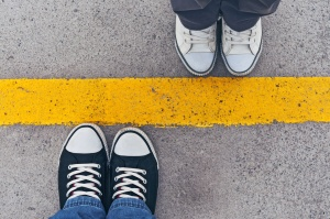 Sneakers from above. Male and female feet in sneakers from above standing at dividing line.